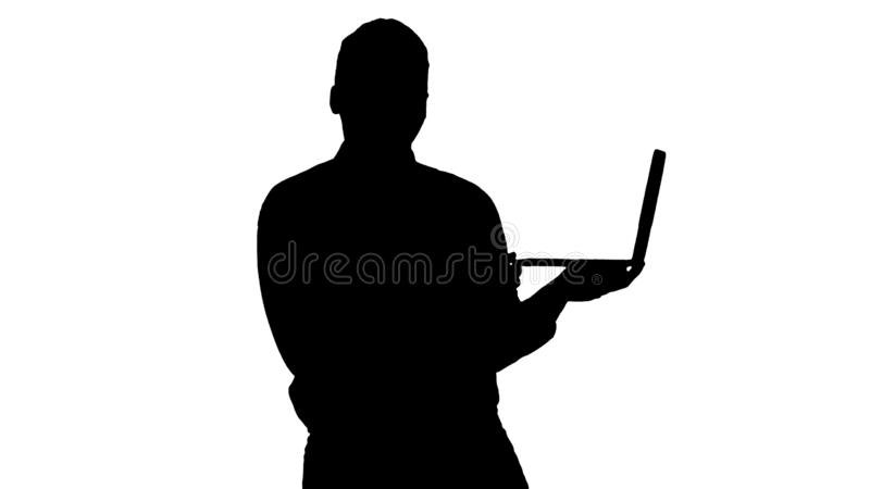 Silhouette Talking to camera young african man with laptop in his hands. royalty free stock images