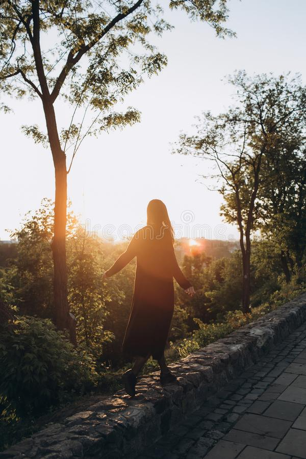 The silhouette of a tall girl in a black robe royalty free stock image