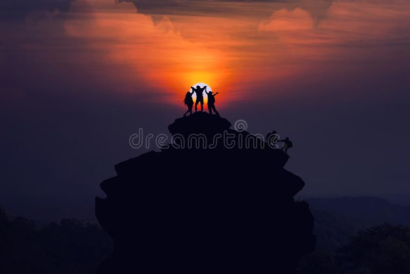 Silhouette of the team hikers climbing up mountain cliff and one. Of them giving helping hand. People helping and Sport and active life team work concept stock image