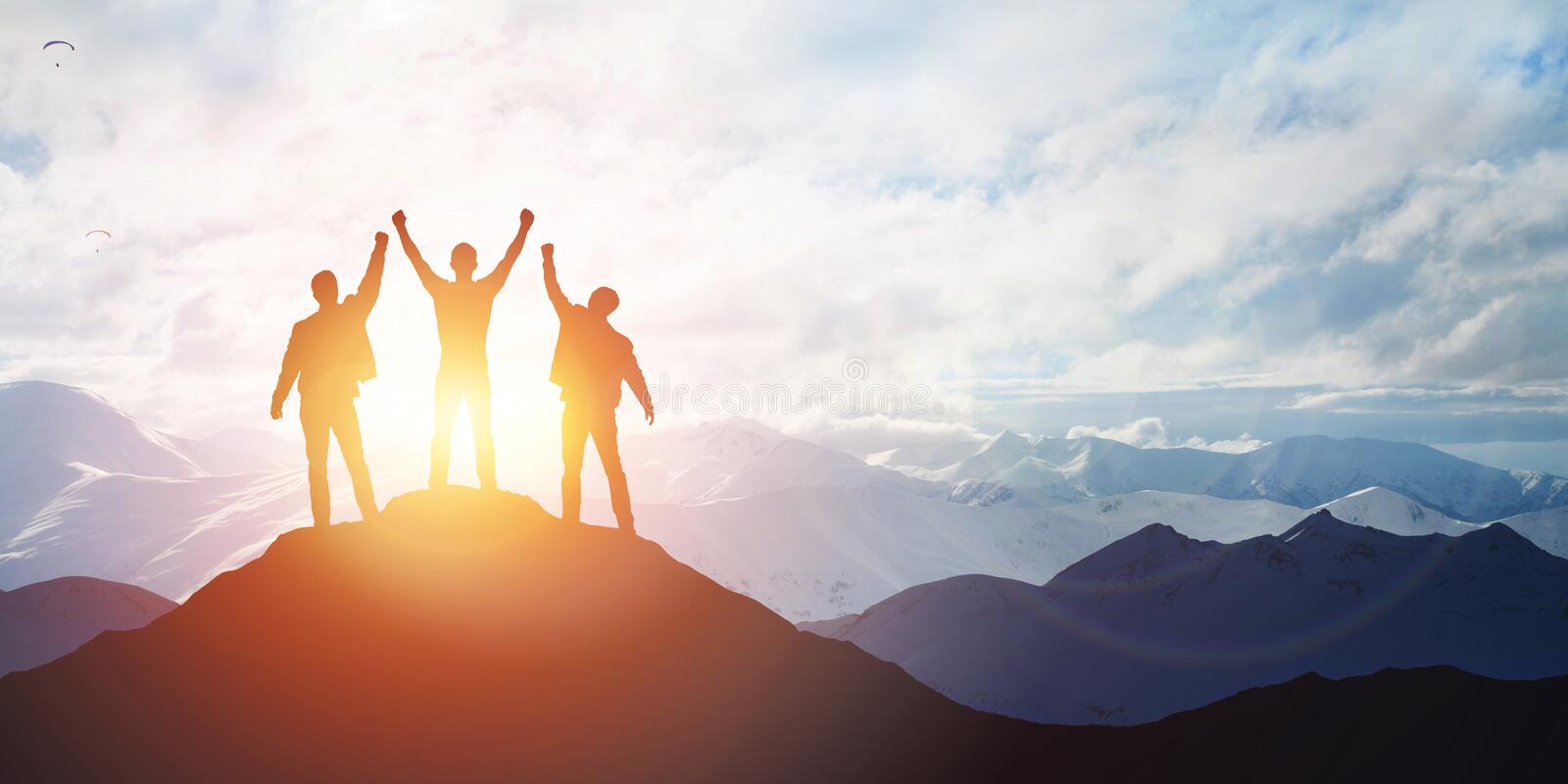 Silhouette of the team on the peak of mountain stock photography