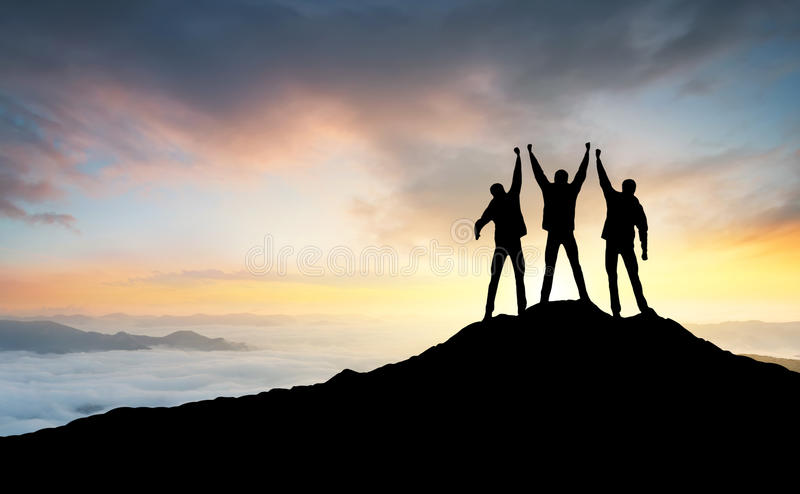 Silhouette of the team on the peak of mountain stock images