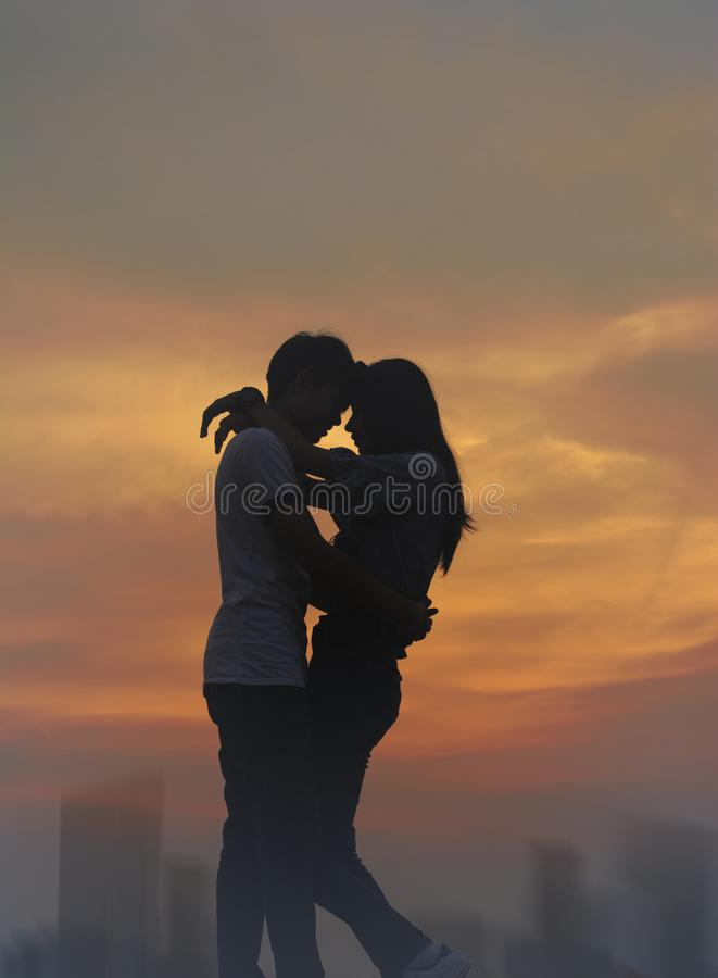 Silhouette teen lovers in romantic scene stock photos