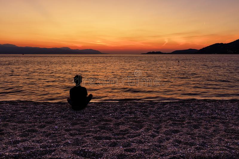 Silhouette of a teenager sitting on the seashore and watching a beautiful, bright sunset on the Gulf of Corinth. A silhouette of a teenager who sits on a beach royalty free stock photos