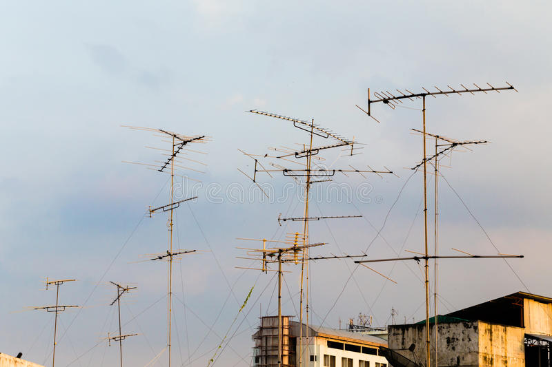 Silhouette, telecommunication towers with TV antennas and satellite dish in sunset. Many home TV antennas and satellite mounted. On the roofs. Photo taken at stock photography