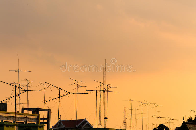 Silhouette, telecommunication towers with TV antennas and satellite dish in sunset. Many home TV antennas and satellite mounted. On the roofs. Photo taken at royalty free stock photography