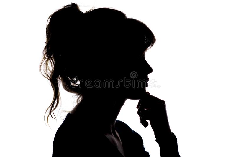 Silhouette of a thoughtful beautiful girl with hand near her chin thinking about solving a problem royalty free stock images