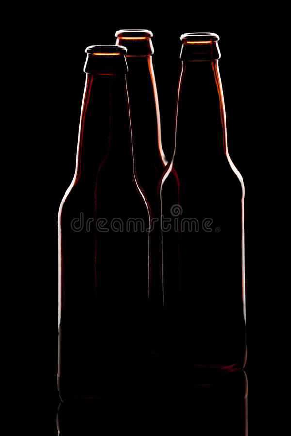 Silhouette of three brown beer bottles royalty free stock photos