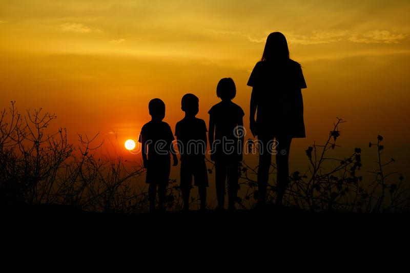 Silhouette of three children and mom standing at mountain. There is a sunset in the background,a. Rt silhouette royalty free stock photo