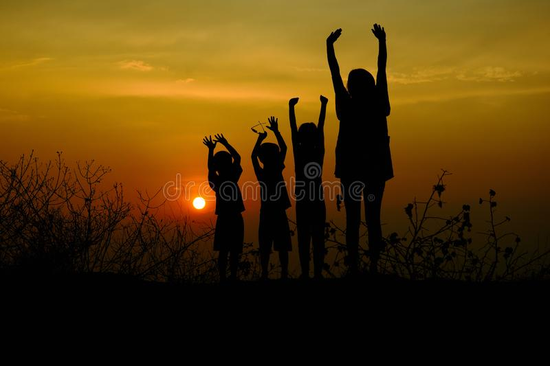 Silhouette of three children and mom standing at mountain. There is a sunset in the background,. Art silhouette stock image