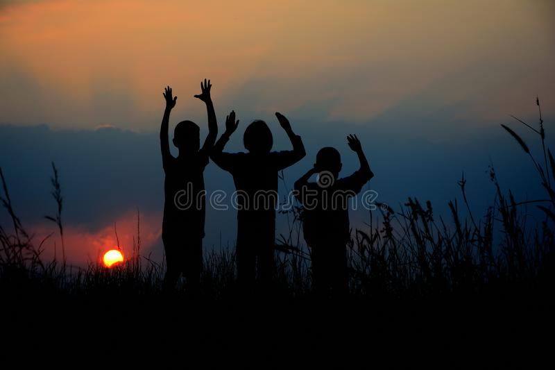 Silhouette of three children standing together. There is a sky at sunset stock photo