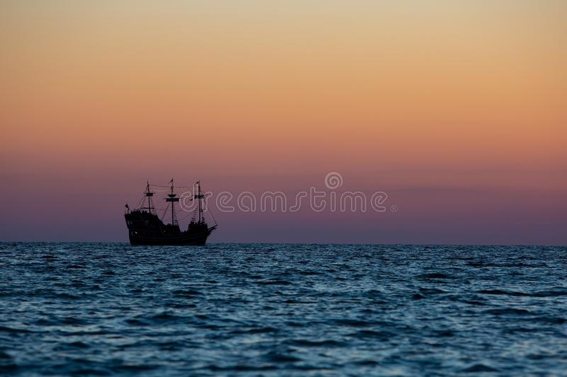 A silhouette of a three mast sailing ship as it heads out into the Gulf. royalty free stock images