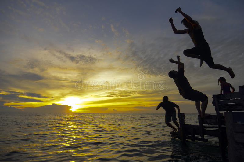 Silhouette of three young man jumping during awesome sunset stock photography