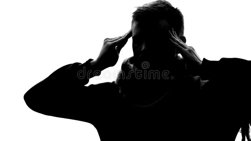 Silhouette of tired young man feeling chronic headache, rubbing temples, fever stock image