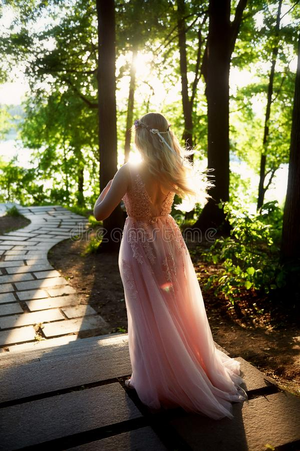 Silhouette tourbillonnant dans le coucher de soleil dans les beaux bois de la jeune mariée dans la robe de pêche avec la dentelle photo stock