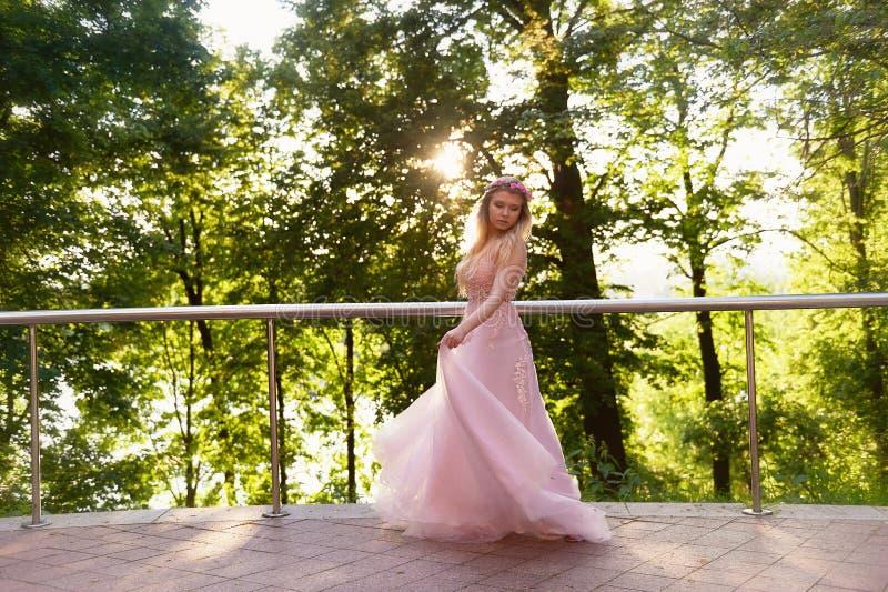 Silhouette tourbillonnant dans le coucher de soleil dans les beaux bois de la jeune mariée dans la robe de pêche avec la dentelle image stock