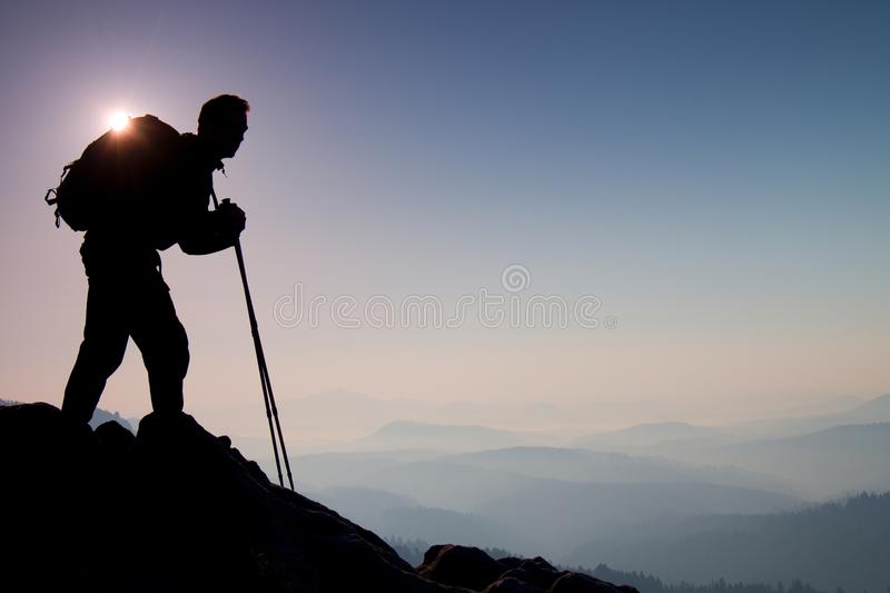 Silhouette of tourist with backpack and poles in hands stand on rocky view point and watching into morning landscape below. stock photo