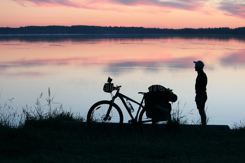 Silhouette of a tourist and a bicycle stock photography