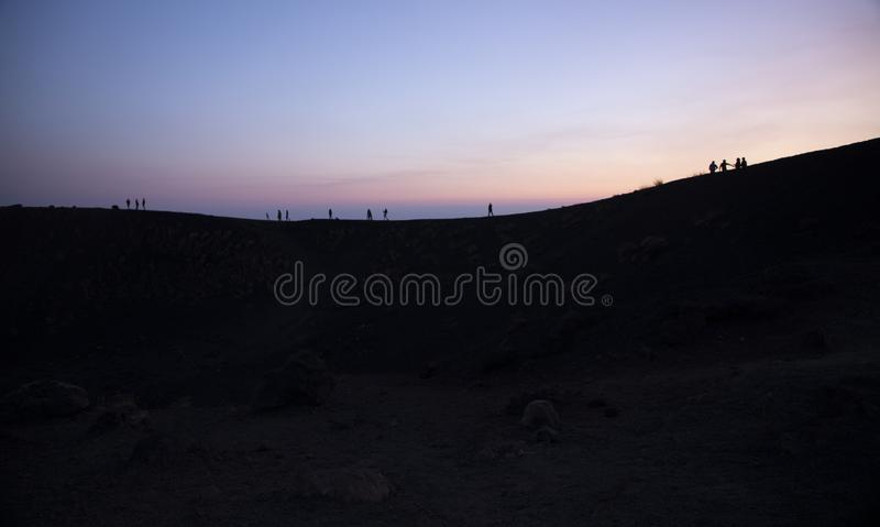 Silhouette tourists on Etna Volcano at sunset light. Silhouette tourists and hikers in the shade and backlight on Etna in the lights of the sunset royalty free stock images