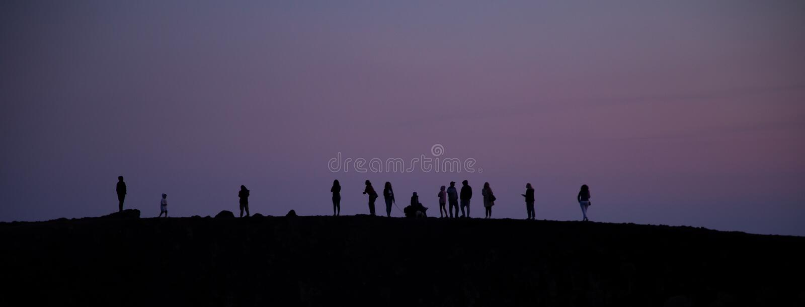 Silhouette tourists on Etna Volcano at sunset light. Silhouette tourists and hikers in the shade and backlight on Etna in the lights of the sunset royalty free stock photos