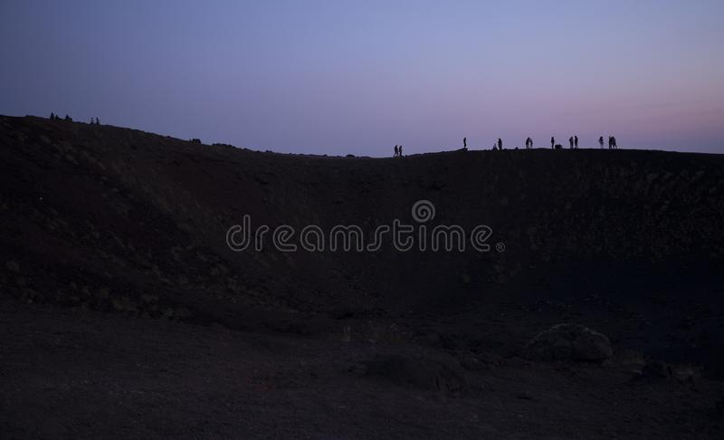 Silhouette tourists on Etna Volcano at sunset light. Silhouette tourists and hikers in the shade and backlight on Etna in the lights of the sunset stock image