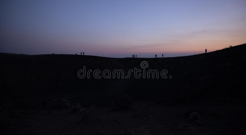 Silhouette tourists on Etna Volcano at sunset light. Silhouette tourists and hikers in the shade and backlight on Etna in the lights of the sunset stock photo