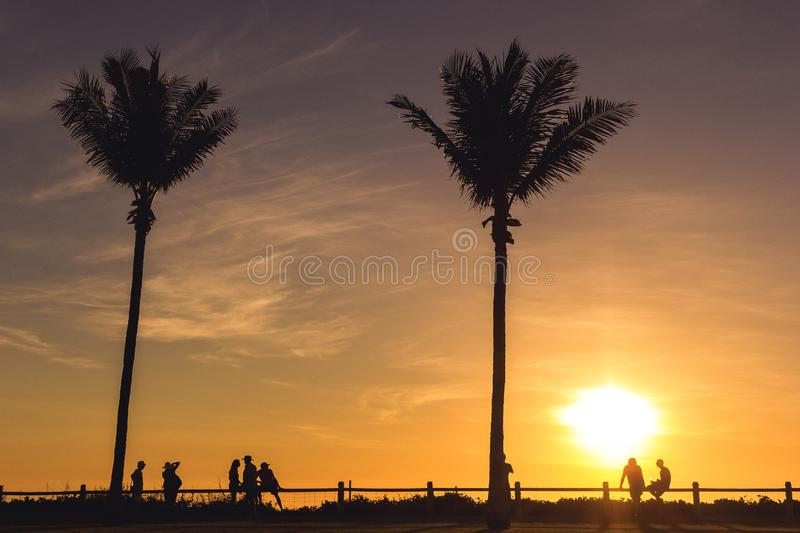 silhouette of tourists, locals and friends enyoing sunset with a drink on the beach in Broome, Western Australia royalty free stock image