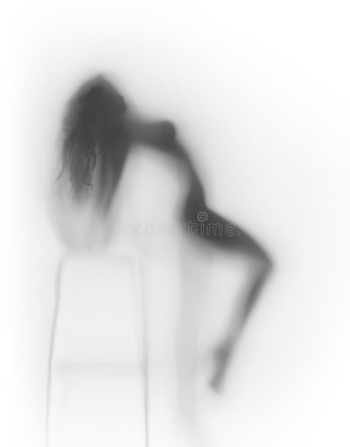 Silhouette très sexy de corps de femme derrière un mur de verre photographie stock libre de droits