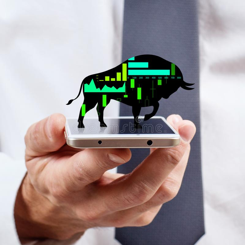 Silhouette of trading bull on the smatrphone screen. Silhouette of trading bull on the smatrphone screen in human hand royalty free stock photography