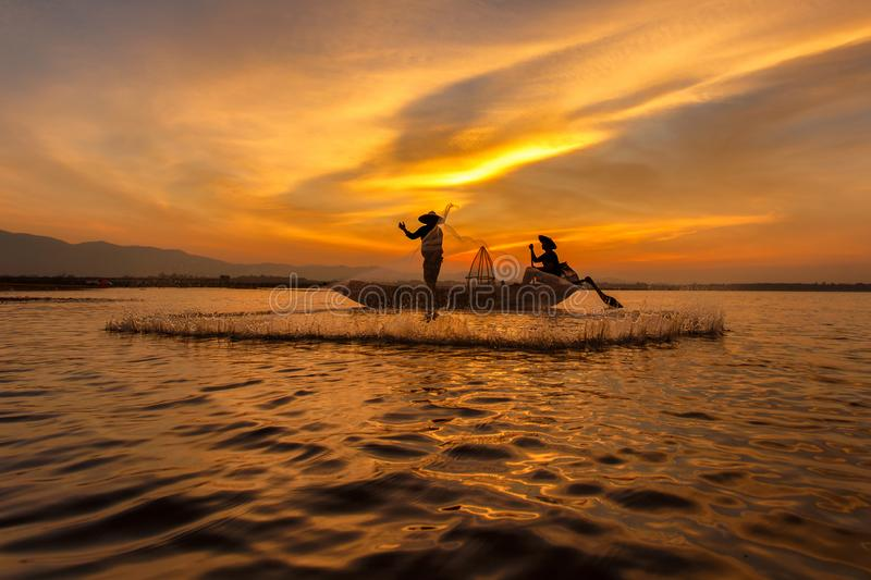 Silhouette of traditional fishermen throwing net fishing inle lake at sunrise time royalty free stock photography