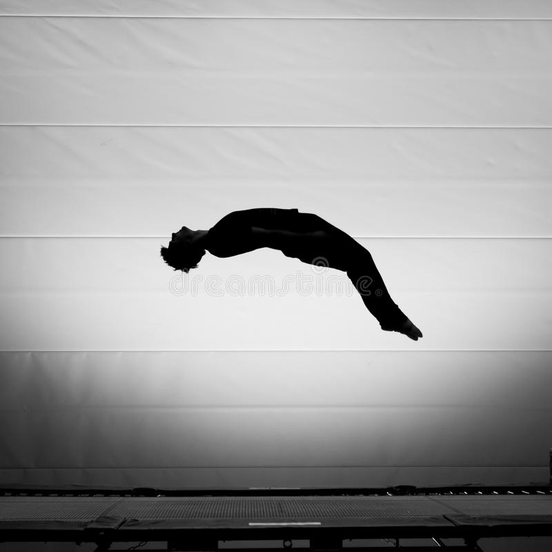 Silhouette on trampoline. Silhouette of gymnast on trampoline stock photo