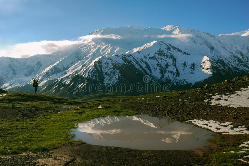 Silhouette the traveler against a background of the Pamir mountains. Snowy peaks, green grass, reflection of mountains in royalty free stock photography