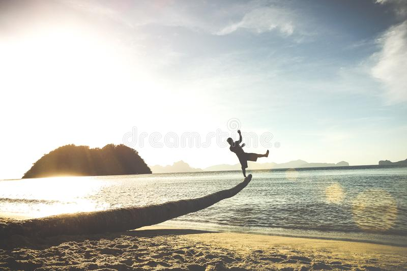 Silhouette of traveler guy on funny jump from palm - Travel wanderlust stock image