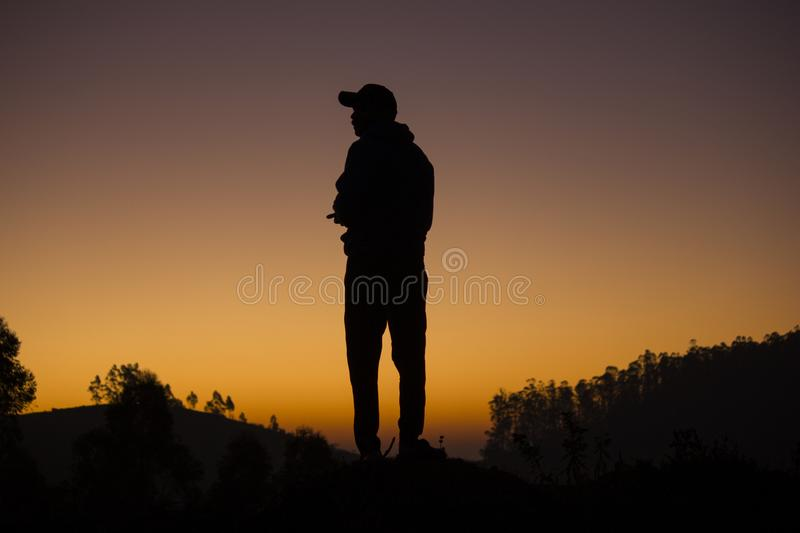 Silhouette of a traveler watching the dramatic sunrise in the valley with orange and purple sky in the background, Ooty. stock photography
