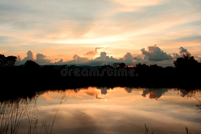 Silhouette of trees with colorful cloud reflection in water sunset background. Beautiful sunset sky royalty free stock image