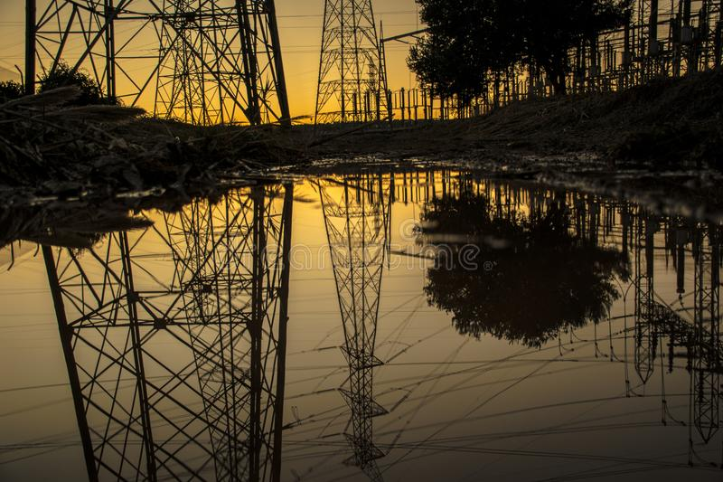 Silhouette of Trees and Electric Tower Reflecting on Body of Water during Sunset stock photos