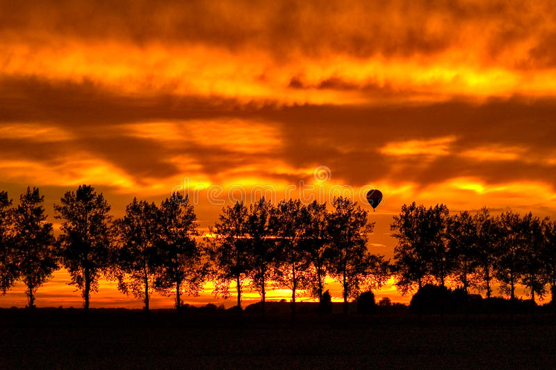 Silhouette with trees and an hotair balloon. A silhouette with trees and an hotair balloon by sunset stock images