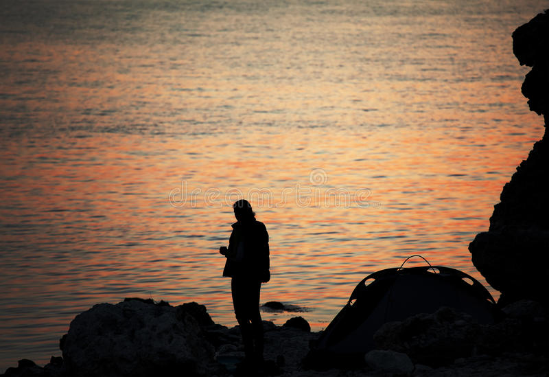 Silhouette of trekker on rocky seashore near camping tent on overnight stay royalty free stock images