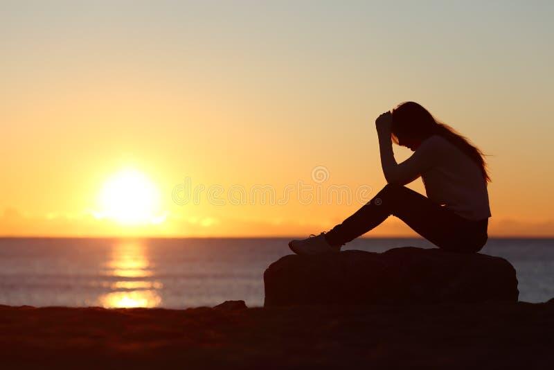 Silhouette triste de femme inquiétée sur la plage images libres de droits