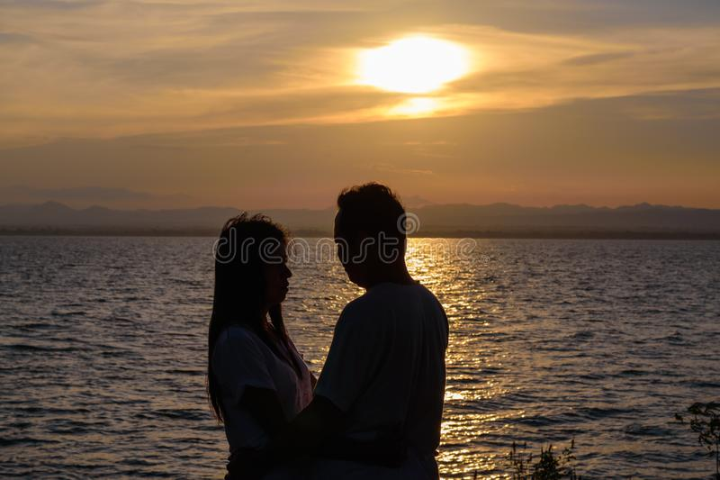 The silhouette of two adults for young couples embrace the waist together happy stock photos