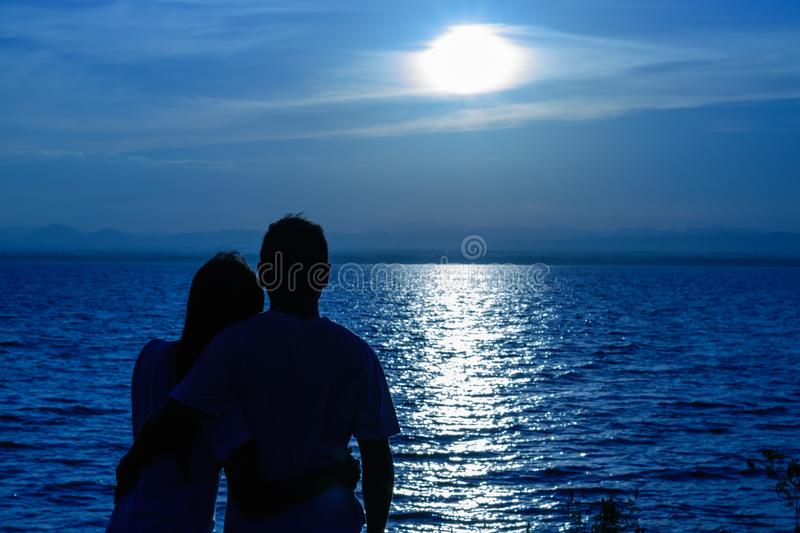 The silhouette of two adults for young couples who are fell on his shoulder bowed together happy. With the beautiful Blue light stock photo