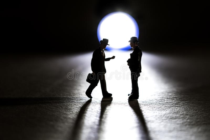 Silhouette of two business figurine walking towards each other in front of a small flashlight royalty free stock image