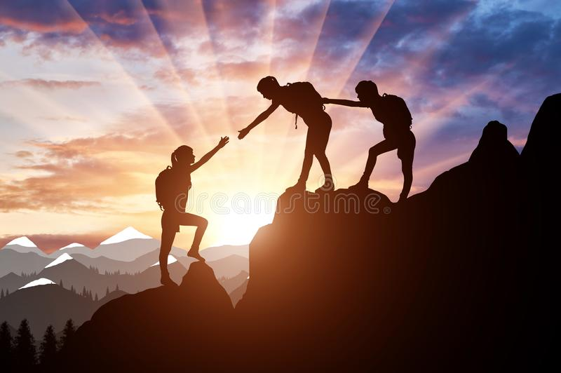 Silhouette of two female mountaineers helping another female mountaineer to overcome the obstacle in the mountains royalty free stock photo