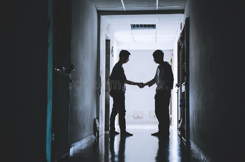 Silhouette two friend shake hands finishing a deal between of the happy and success friendship stock photos