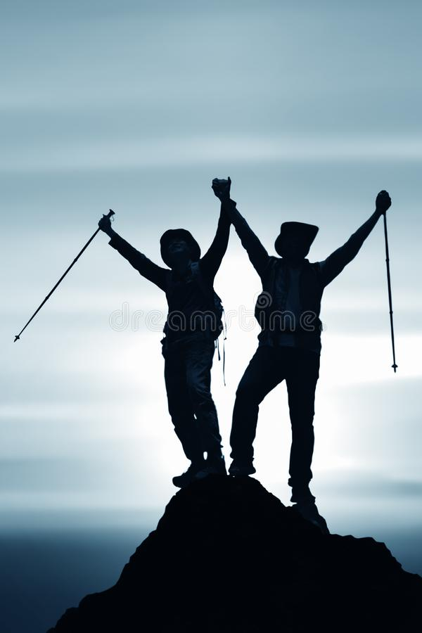 Silhouette of two friends having achievement climbing up mountain to the peak together royalty free stock image