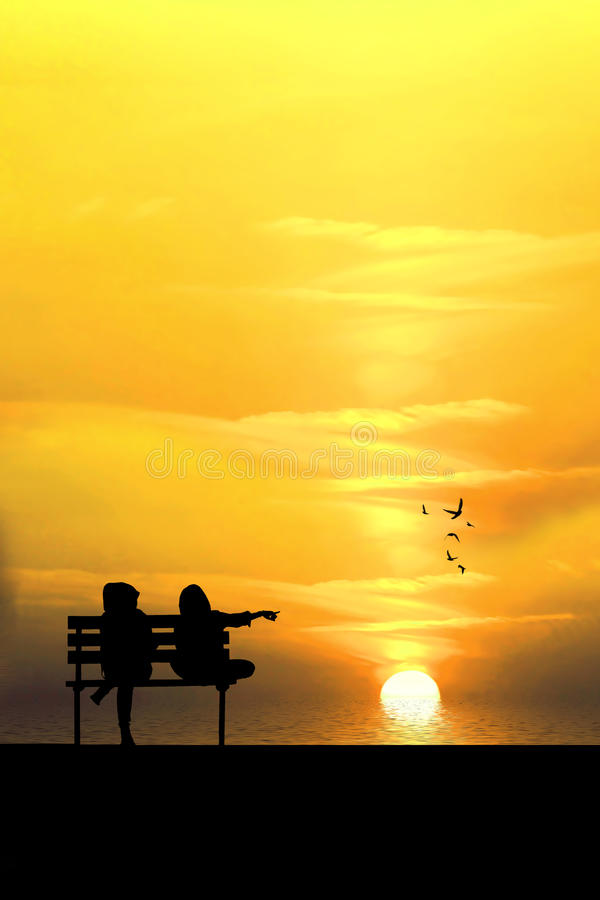 Silhouette of two friends sitting on wood bench near beach stock images
