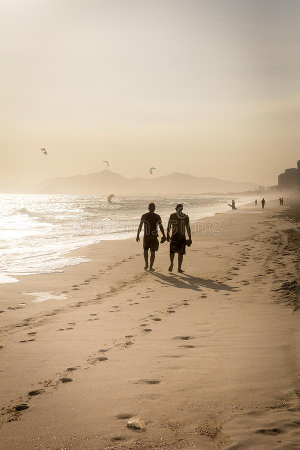 Silhouette of two friends walking on the beach during sunset royalty free stock photo