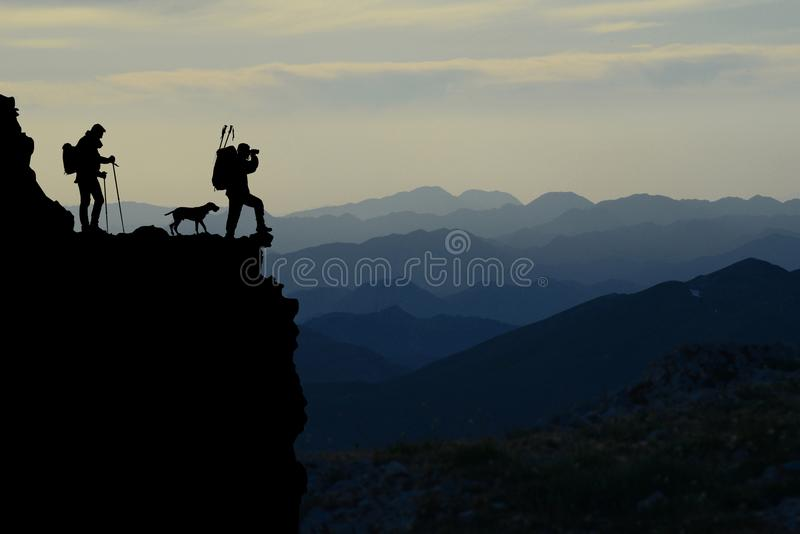 Mountain hikers silhouette. Silhouette of two hikers and a dog in profile on the edge of a cliff, overlooking a mountain range stock photos