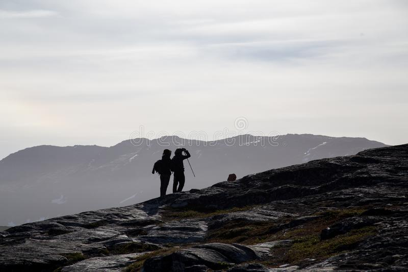 Silhouette of two hikers. Ilulissat, Greenland - July 8, 2018: Silhouette of two hikers in a rocky landscape stock images