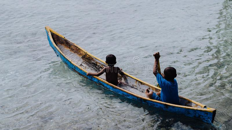 Silhouette of two local boys in a boat on Arborek Island in Raja Ampat, West Papua, Indonesia, near the famous Manta. Point dive spot stock photos