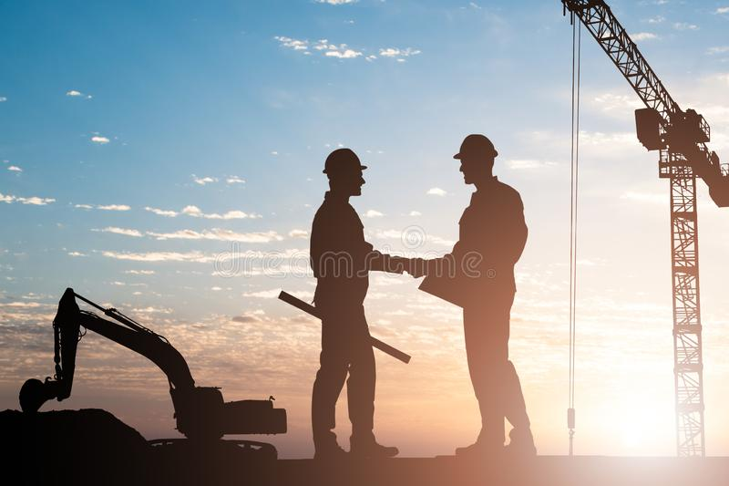 Silhouette Of Two Male Architect Shaking Hands royalty free stock photos